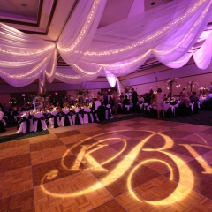 Monogram rotating on dance floor with colored LED uplighting